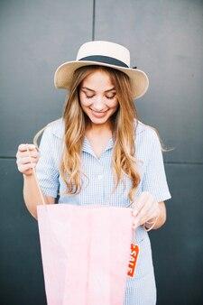 Vrouw die binnenkant van het winkelen zakken kijkt