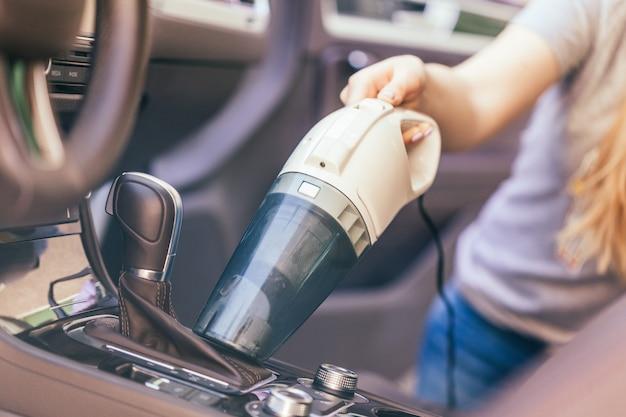 Vrouw die binnenland van auto schoonmaken die stofzuiger met behulp van