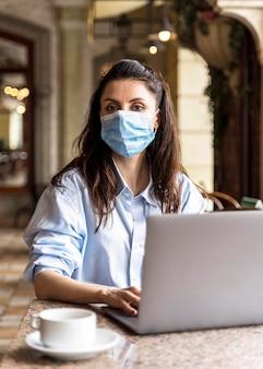 Vrouw die binnenshuis werkt terwijl ze een gezichtsmasker draagt