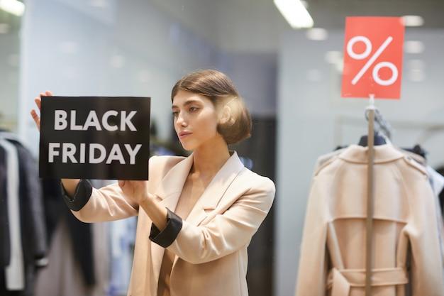 Vrouw die black friday-teken in opslag hangen
