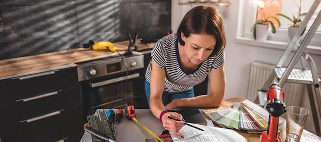 Vrouw die blauwdruk controleert bij nieuwe keuken