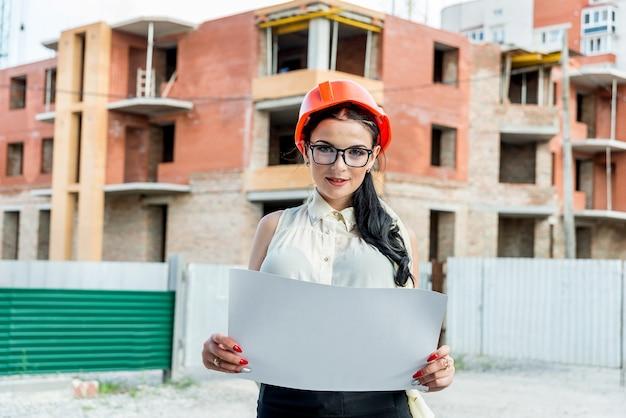 Vrouw die blauwdruk op bouwwerfachtergrond onderzoekt