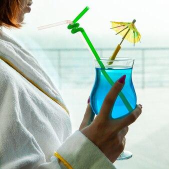 Vrouw die blauwe cocktail houdt kijkend buiten van venster in badjas.
