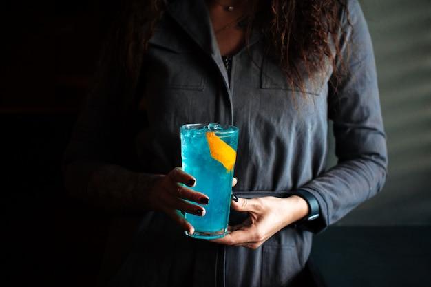 Vrouw die blauwe cocktail in een longdrinkbal met ijs houdt