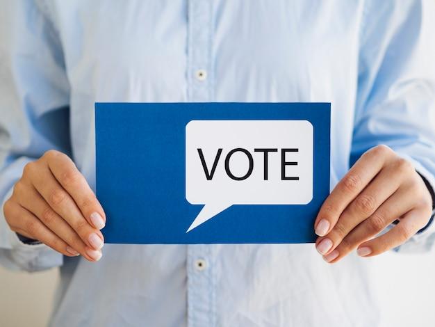 Vrouw die blauwe kaart met de bel van de stemtoespraak houdt