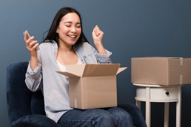 Vrouw die blij is met haar online aankoop die ze heeft ontvangen