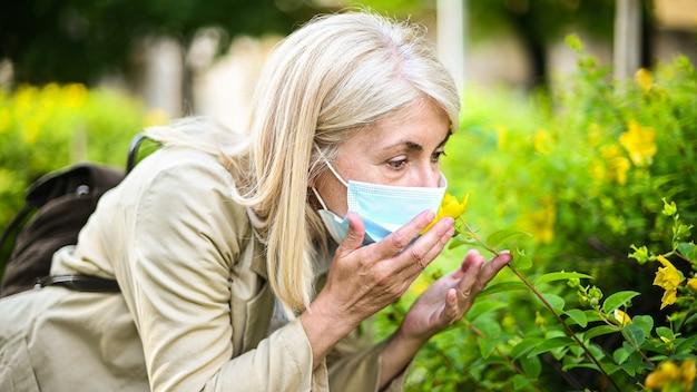 Vrouw die bloem probeert te ruiken terwijl het dragen van een masker