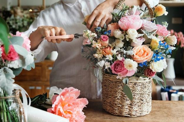 Vrouw die bloemen aan het voorbereiden en schikken is