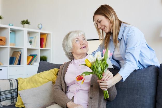 Vrouw die bloemen geeft aan moeder
