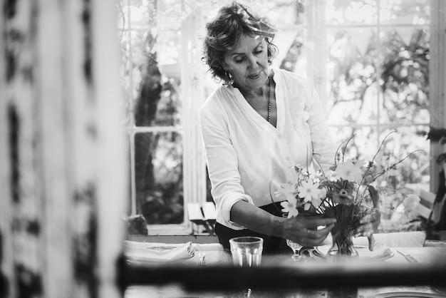 Vrouw die bloemen in een serre schikt