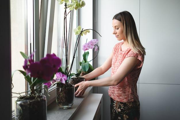 Vrouw die bloemen in het huis schikt