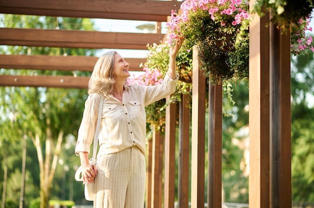 Vrouw die bloemen in het zomerpark bewondert
