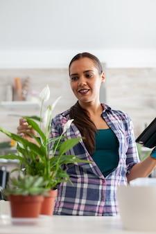Vrouw die bloemen in huiskeuken controleert en tabletpc gebruikt