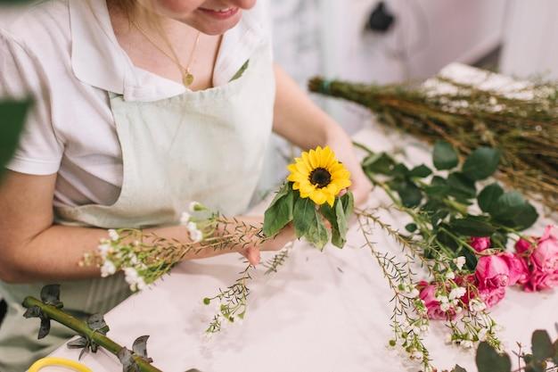 Vrouw die bloemen samen in boeket samenstellen
