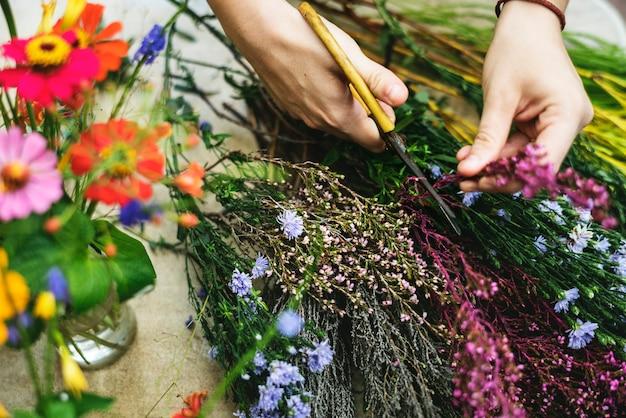 Vrouw die bloemen schikt en verfraait