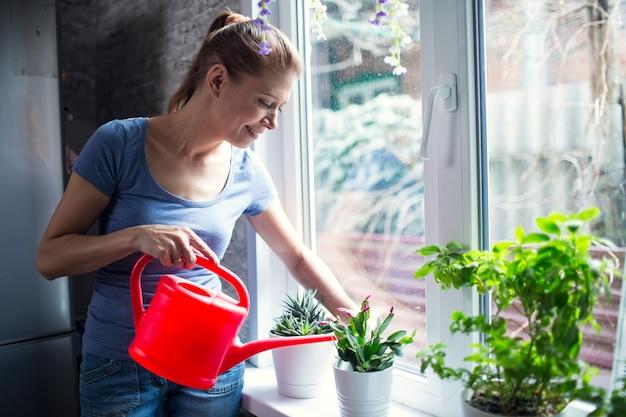 Vrouw die bloemen thuis water geeft op het raam