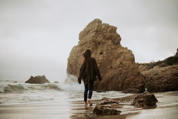 Vrouw die blootvoets bij een strand loopt