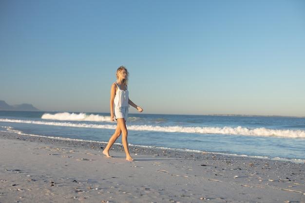 Vrouw die blootvoets op het strand loopt