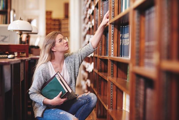 Vrouw die boeken in bibliotheek onderzoekt