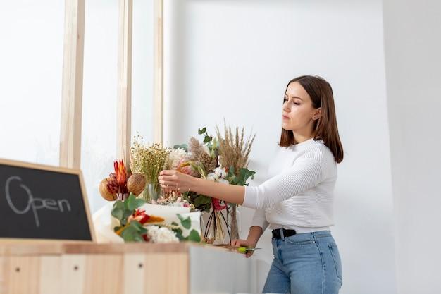 Vrouw die boeketten van bloem schikken om spoedig zaken te openen