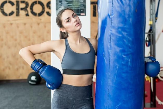 Vrouw die bokszak omhelst