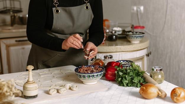 Vrouw die bollen maakt bij keuken met ingrediënten
