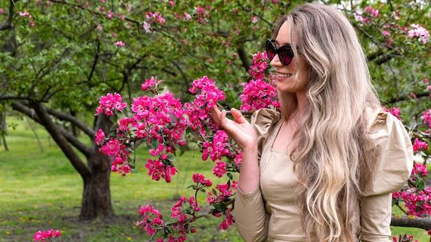 Vrouw die boom met roze bloemen aanraakt