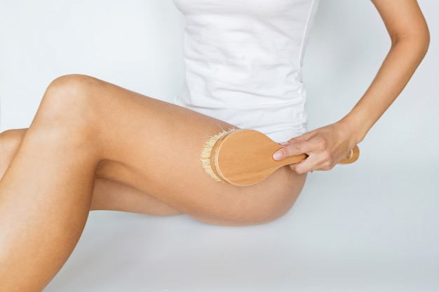 Vrouw die borstel voor het masseren van lichaam op wit gebruikt