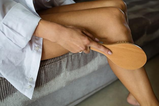 Vrouw die borstel voor thuis het masseren van lichaam gebruikt