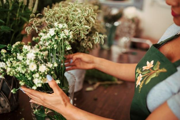 Vrouw die bos van bloemen in vaas schikken