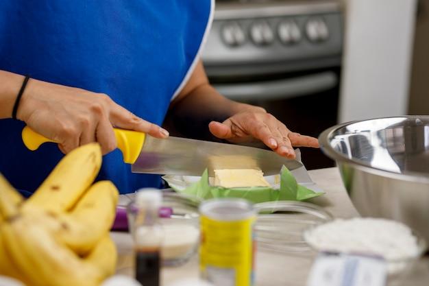 Vrouw die boter snijdt om een bananenpannenkoek te bereiden thuisbakconcept