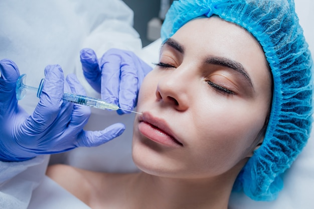 Vrouw die botox-injectie ontvangt in spa, injectie van botox in lip.