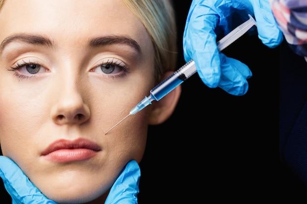 Vrouw die botox injectie op haar lippen ontvangt