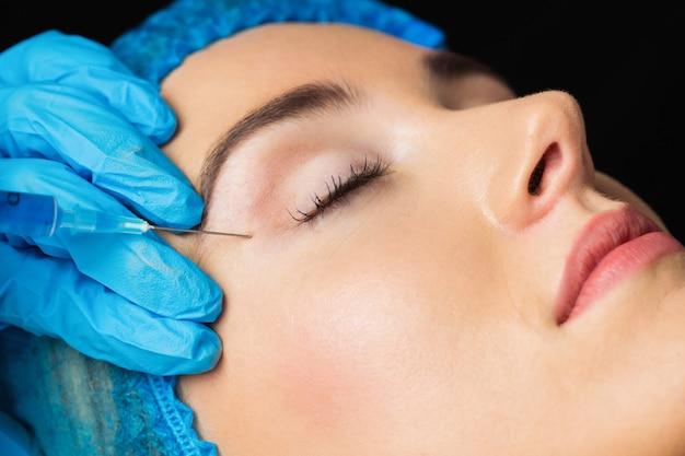 Vrouw die botox injectie op haar voorhoofd ontvangt