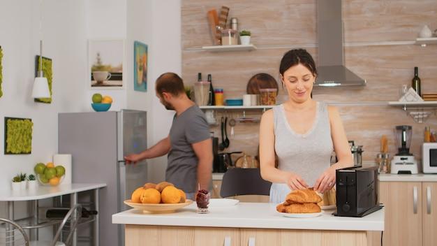 Vrouw die broodrooster gebruikt om brood in de keuken te roosteren tijdens het ontbijt. jonge huisvrouw die thuis een ochtendmaaltijd kookt, vrolijk met genegenheid en liefde