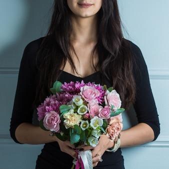 Vrouw die bruids bloemboeket bevordert