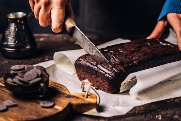 Vrouw die bruin chocoladebrood snijdt