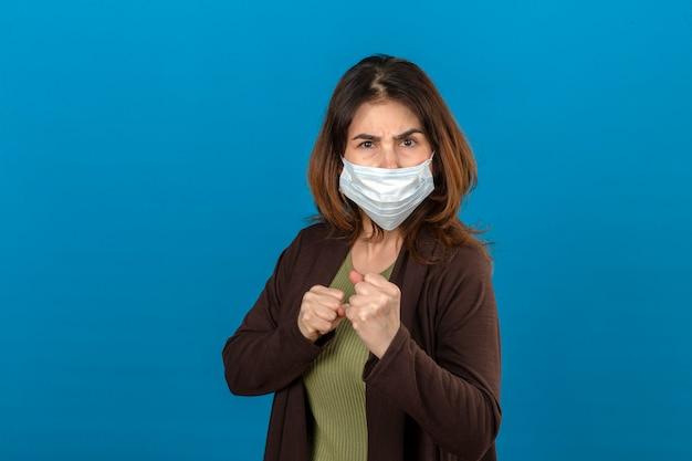 Vrouw die bruin vest in medisch beschermend masker draagt dat zich met in dozen doende vuisten kijkt en klaar aan te vallen of te verdedigen
