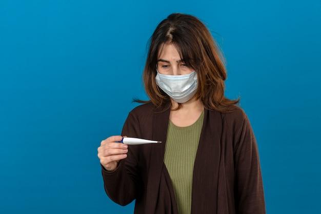 Vrouw die bruin vest in medisch beschermend masker draagt dat ziek het houden van digitale thermometer kijkt die het met droevige uitdrukking op gezicht over geïsoleerde blauwe muur bekijkt