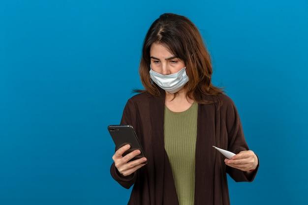 Vrouw die bruine cardigan in medische beschermende smartphone van de maskerholding en digitale thermometer in handen dragen die aan iemand roepen die zenuwachtig over geïsoleerde blauwe muur kijken