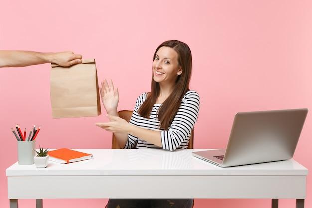 Vrouw die bruine duidelijke lege lege ambachtelijke papieren zak neemt, werk op kantoor met pc-laptop geïsoleerd op roze achtergrond. koeriersdienst voor het bezorgen van voedselproducten van winkel of restaurant naar kantoor. ruimte kopiëren.