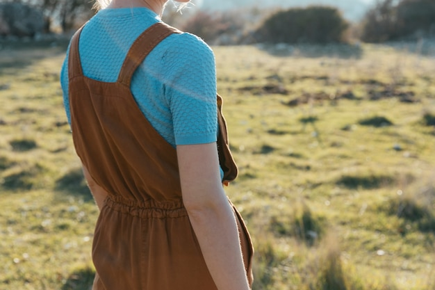 Vrouw die bruine overall met t-shirt draagt
