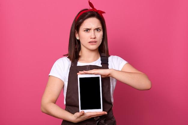 Vrouw die bruine schort draagt, die het lege lege scherm met exemplaarruimte toont voor reclame of bevordering