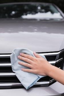 Vrouw die buiten auto schoonmaakt