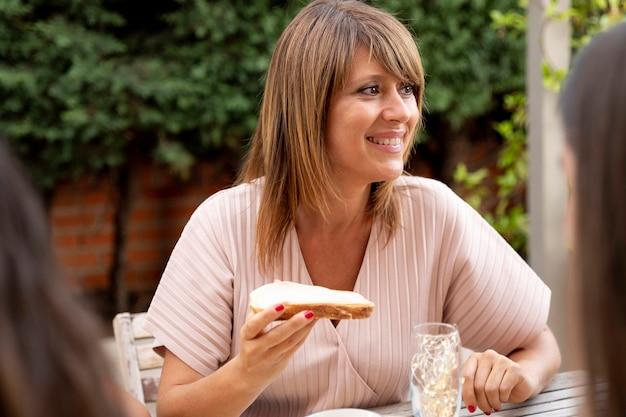 Vrouw die buiten luncht terwijl ze wordt omringd door familie