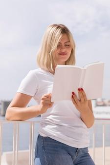 Vrouw die buitenshuis een boek leest