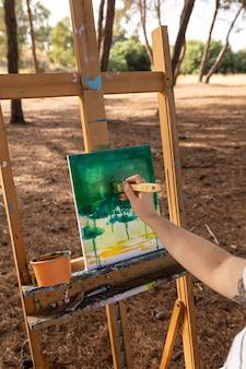 Vrouw die buitenshuis landschap op canvas schildert