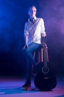 Vrouw die bureauoverhemd draagt dat een akoestische gitaar houdt