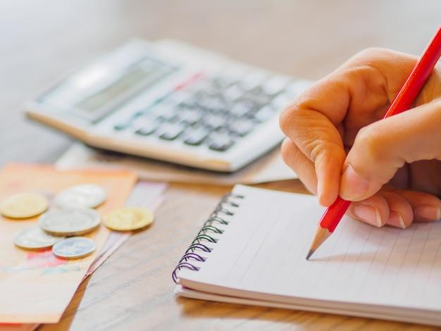 Vrouw die calculator gebruiken en over kosten op bureau thuis bureau denken