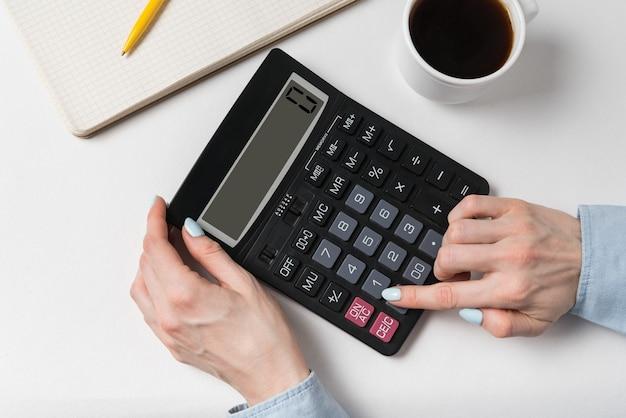 Vrouw die calculator gebruikt. documenten, kopje koffie en rekenmachine op een wit